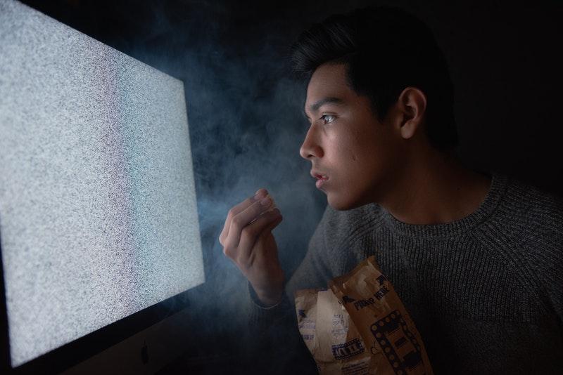 Homme-fatigue-regarde-ecran-grignote-sucre